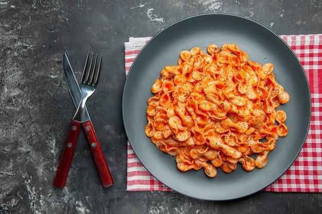 Oben blick auf einfache pasta-mahlzeit zum abendessen auf einem schwarzen teller und besteck auf einem roten, gestreiften handtuch auf dunklem hintergrund