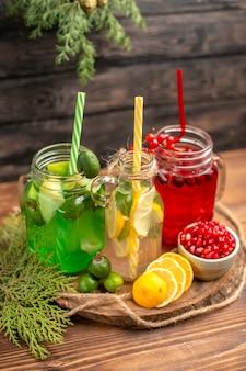 Oben blick auf frische bio-säfte in flaschen, serviert mit tuben und früchten auf einem holzbrett