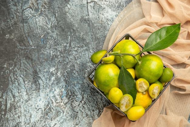 Oben blick auf frische kumquats und zitronen in einem schwarzen korb auf handtuch auf grauem hintergrund