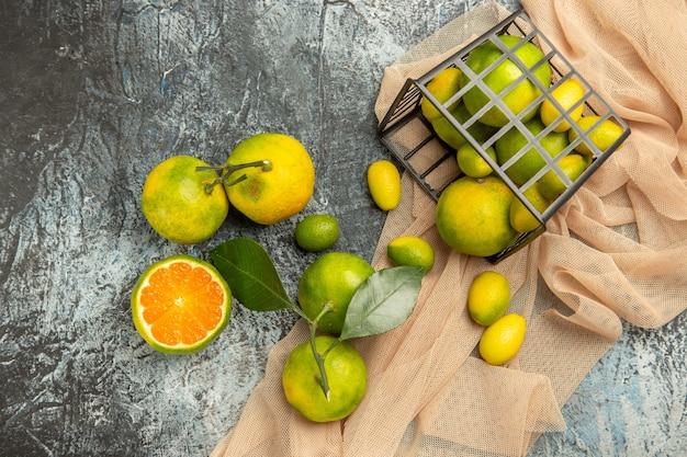 Oben blick auf frische kumquats und zitronen in einem schwarzen korb auf handtuch und vier zitronen auf grauem hintergrundmaterial