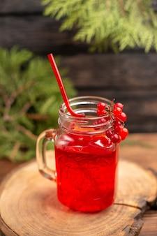 Oben blick auf frischen johannisbeersaft in einem glas serviert mit rohr auf einem holzbrett