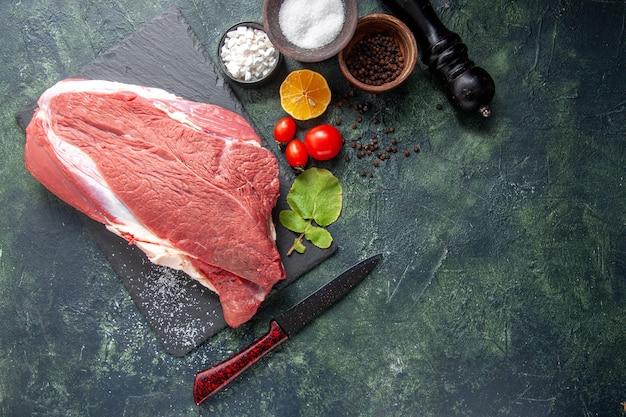 Oben blick auf frisches rohes rotes fleisch auf schwarzem tablett pfeffer salz zitrone holzhammer auf dunklem hintergrund