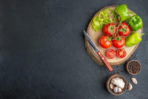 Oben blick auf ganze geschnittene gehackte grüne paprika und frische tomatenmesser auf holzbrett auf der linken seite auf schwarzer oberfläche