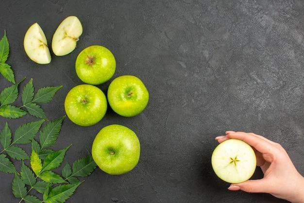 Oben blick auf ganze und gehackte frische grüne äpfel und minze auf schwarzem hintergrund