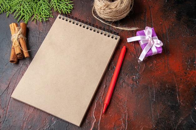 Oben blick auf geschlossenes notizbuch zimtlimetten und geschenk auf dunklem hintergrund