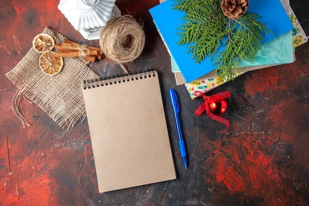 Oben blick auf gestapelte notizbücher und kugelschreiber aus seil-zimt-limonen-nadelkegeln auf dunklem hintergrund