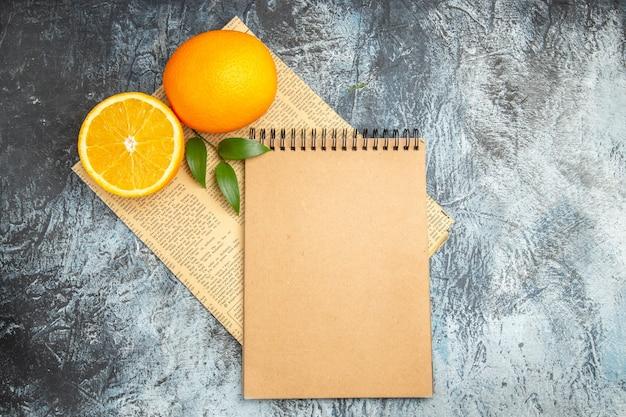 Oben blick auf halbierte und ganze frische orange mit blättern und notizbuch auf zeitung auf grauem hintergrund