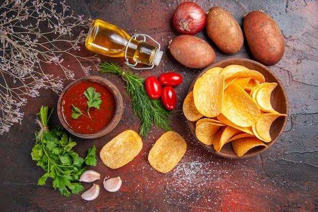 Oben blick auf hausgemachte köstliche knusprige kartoffelchips in einer kleinen braunen schüssel kartoffeln ölflaschengrün und tomaten-knoblauch-ketchup auf dunklem tisch