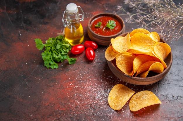 Oben blick auf hausgemachte leckere knusprige kartoffelchips in einer kleinen braunen schüssel ölflasche grüner tomatenketchup auf dunklem tisch