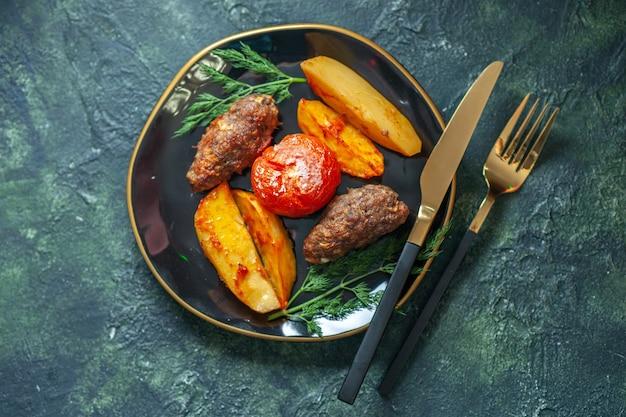 Oben blick auf köstliche fleischkoteletts, die mit kartoffeln und tomaten auf einem schwarzen teller gebacken werden, serviert mit grünem besteck auf grünschwarzem hintergrund