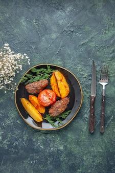 Oben blick auf köstliche fleischkoteletts, die mit kartoffeln und tomaten auf einem schwarzen tellerbesteck gebacken werden, weiße blumen auf grün-schwarzem mischfarbenhintergrund