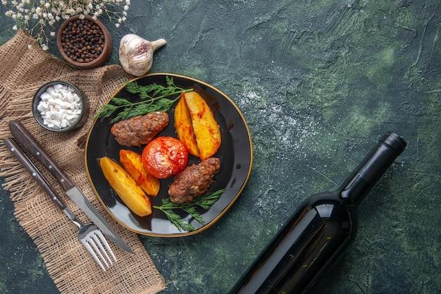Oben blick auf köstliche fleischkoteletts, die mit kartoffeln und tomaten auf einer schwarzen platte gebacken werden, gewürze knoblauchbesteck, wein auf grünschwarzem mischfarbenhintergrund