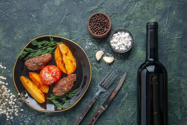 Oben blick auf köstliche fleischkoteletts, die mit kartoffeln und tomaten auf einer schwarzen platte gebacken werden, gewürzknoblauch-weinflasche auf grün-schwarzem mischfarbenhintergrund