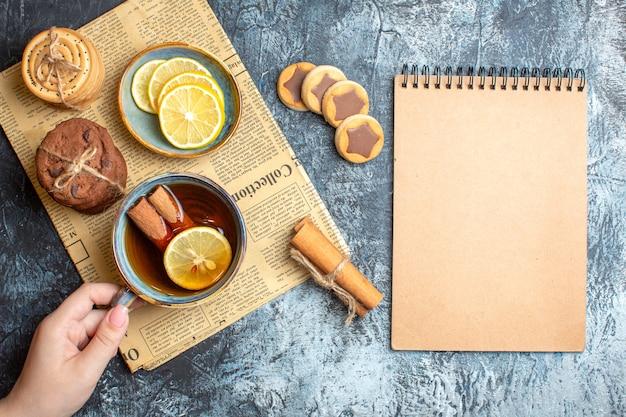 Oben blick auf köstliche kekse und hand, die eine tasse schwarzen tee mit zimt auf einer alten zeitung hält holding