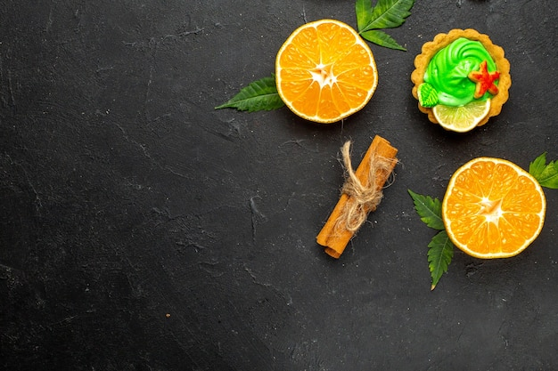 Oben blick auf köstliche kekse, zimtlimetten und halbgeschnittene orangen mit blättern auf dunklem hintergrund