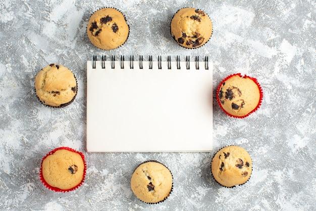 Oben blick auf köstliche kleine cupcakes mit schokolade um das geschlossene notizbuch auf der eisoberfläche