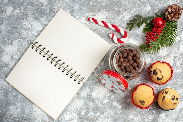 Oben blick auf köstliche kleine cupcakes und schokolade in einem glastopf und tannenzweigen neben dem offenen notizbuch auf der eisoberfläche