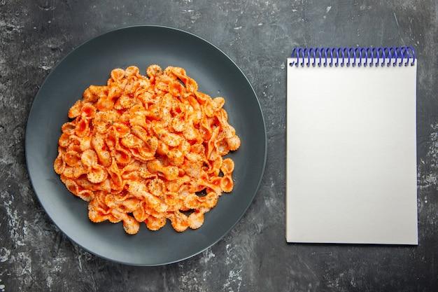 Oben blick auf köstliche pasta-mahlzeit auf einem schwarzen teller zum abendessen und notizbuch auf dunklem hintergrund