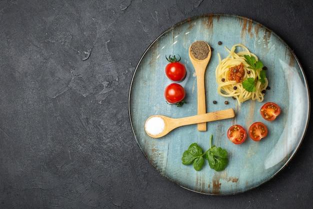 Oben blick auf köstliche pastagerichte mit fleischgemüse-tomaten auf einem teller auf der linken seite auf schwarzem hintergrund