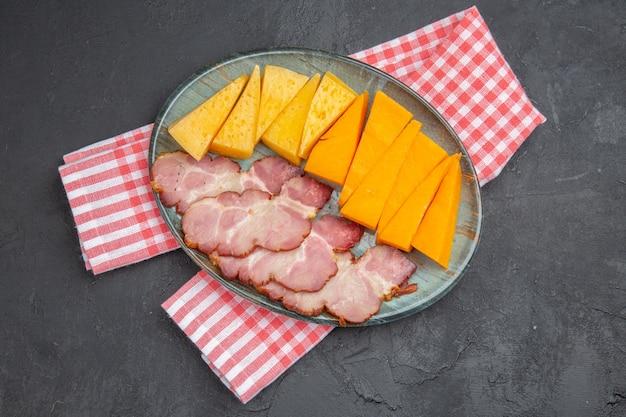 Oben blick auf köstliche snacks auf rotem, halb gefaltetem handtuch auf schwarzem hintergrund to