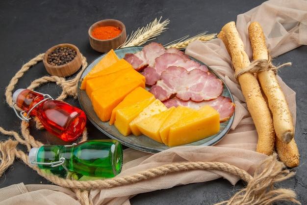 Oben blick auf köstliche snacks gefallene flaschen paprika auf handtuch und seil auf schwarzem hintergrund