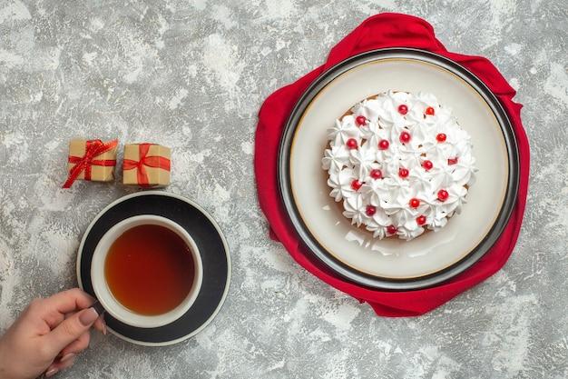 Oben blick auf köstlichen cremigen kuchen, der mit früchten auf einer roten handtuchhand dekoriert ist, die eine tasse schwarzen tee hält, kleine geschenkboxen auf eishintergrund