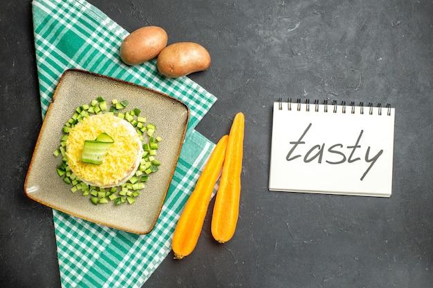 Oben blick auf köstlichen salat, serviert mit gehackter gurke auf halb gefalteten grünen, abgestreiften handtuchkarotten und kartoffeln neben einem notizbuch mit leckerer beschriftung auf dunklem hintergrund
