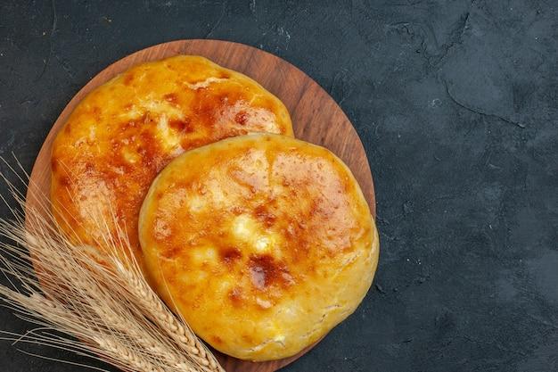 Oben blick auf köstliches frisch gebackenes gebäck und spike auf dem holzbrett auf dunklem schwarzgrund