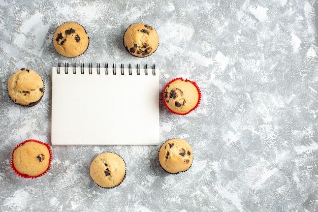 Oben blick auf leckere kleine cupcakes mit schokolade um geschlossenes notizbuch auf der rechten seite auf eisfläche