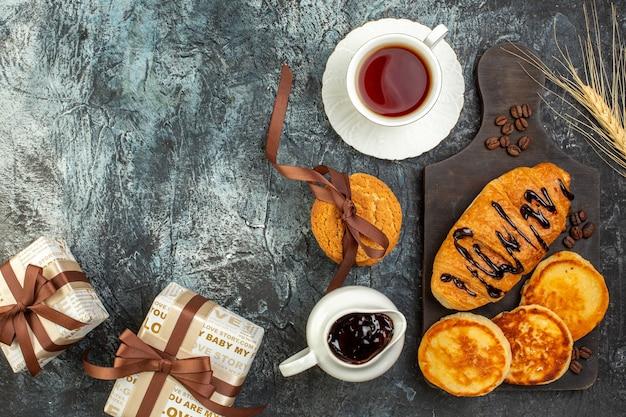 Oben blick auf leckeres frühstück mit pfannkuchen, croisasant, gestapelte keks-geschenkboxen auf dunklem tisch