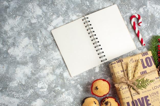 Oben blick auf offenes notizbuch und schönes weihnachtsgeschenk mit liebesaufschrift kleine cupcakes und tannenzweige dekorationszubehör nadelbaumkegel auf eisoberfläche