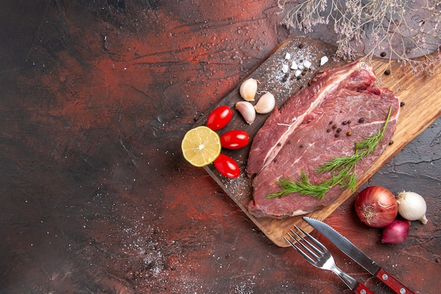 Oben blick auf rotes fleisch auf holzbrett und knoblauch grüne zitronenzwiebelgabel und messer auf dunklem hintergrund