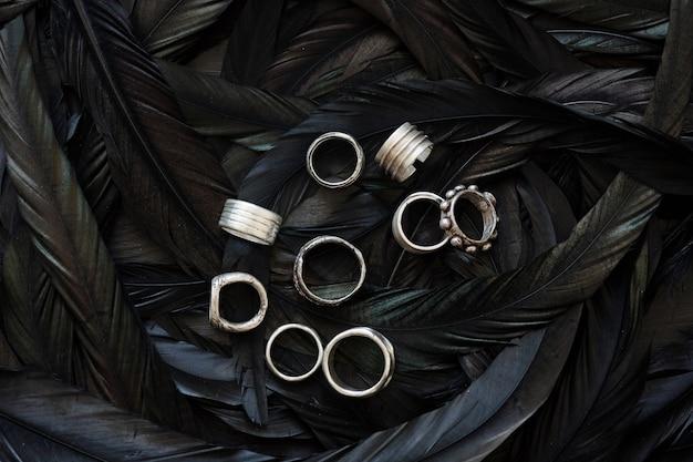Oben blick auf schöne handgefertigte silberringe, die auf einem juweliergeschäft mit schwarzen federn platziert sind