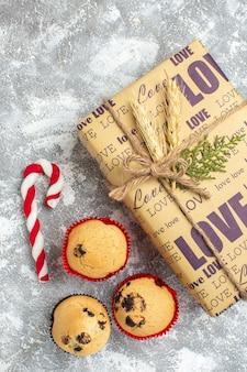 Oben blick auf schönes weihnachtsgeschenk mit liebesaufschrift kleine cupcakes süßigkeiten auf eisoberfläche