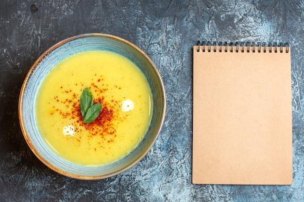 Oben blick auf spiralnotizbuch und einen blauen topf mit leckerer suppe auf blauem tisch