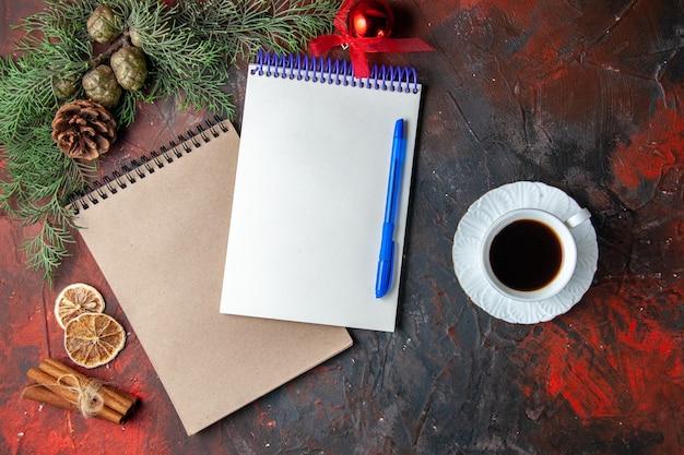 Oben blick auf spiralnotizbücher mit stift-tannenzweig-zimt-limonen-koniferenkegel und einer tasse schwarzem tee auf dunklem hintergrund