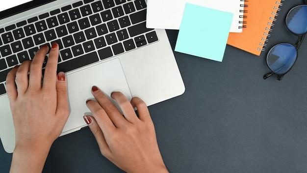 Oben blick auf stilvolle frauenhände, die auf laptop-computer tippen.