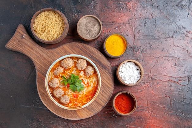 Oben blick auf tomaten-fleischbällchen-suppe mit nudeln in einer braunen schüssel und verschiedenen gewürzen auf dunklem hintergrund