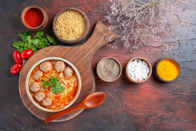 Oben blick auf tomaten-fleischbällchen-suppe mit nudeln in einer braunen schüssel und verschiedenen gewürzen ölflasche zwiebel knoblauch auf dunklem hintergrund stockfoto