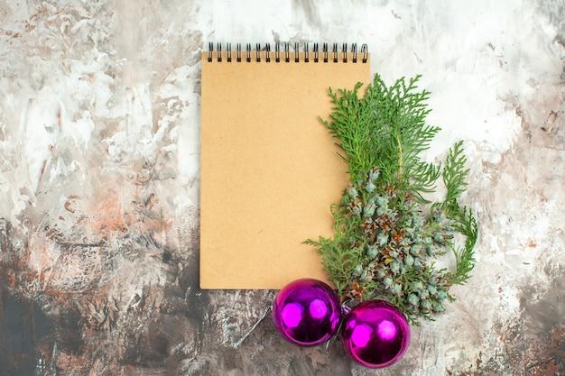 Oben blick auf weihnachtszubehör und skraft-spiralnotizbuch auf gemischtem farbhintergrund