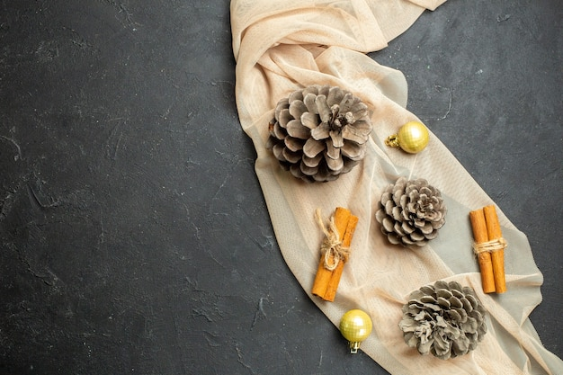 Oben blick auf zimt-limonen-dekorationszubehör und drei koniferenzapfen auf nacktem farbtuch auf schwarzem hintergrund