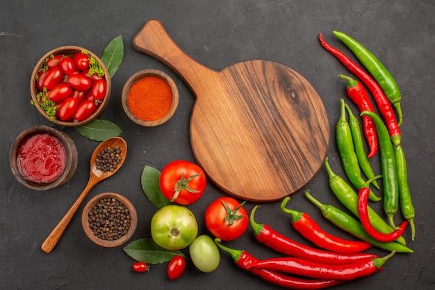 Oben entfernte ansicht eine schüssel kirschtomaten scharfe rote und grüne paprikaschoten und tomaten lorbeerblätter schalen mit ketchup-paprika-pulver und schwarzem pfeffer und ein schneidebrett auf dem boden