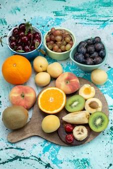Oben entfernte ansicht fruchtzusammensetzung geschnitten und ganz auf dem hellen schreibtischfrucht exotischen kekszucker