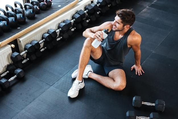 Oben foto von fitness-mann, der im fitnessstudio sitzt. mit flasche und gewicht
