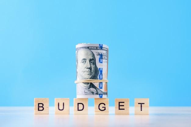 Oben gerollte dollarscheine und wortbudget auf einem blauen hintergrund. finanzbuchhaltungskonzept