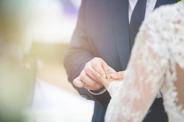 Oben geschlossen vom bräutigam setzte hochzeitsdiamantring auf brautfinger in hochzeitszeremonie ein, um heirat festzulegen.