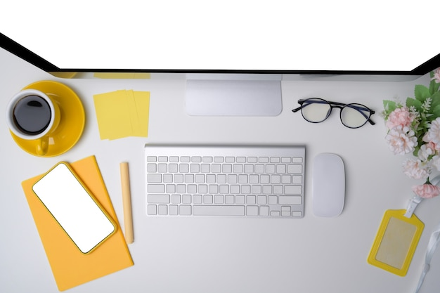 Oben moderner arbeitsplatz mit computer, handy und kaffeetasse auf weißem schreibtisch.