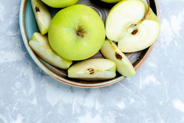 Oben nähere ansicht frische grüne äpfel in scheiben geschnitten und ganze früchte auf leichter oberfläche obst frisch ausgereift reifes lebensmittel vitamin