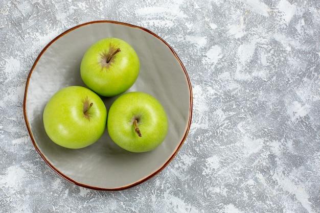 Oben nähere ansicht frische grüne äpfel innerhalb platte auf weißer oberfläche frisches reifes mildes fruchtnahrungsmittelvitamin
