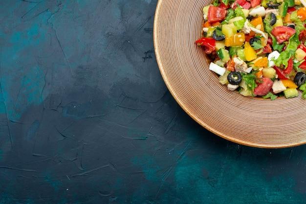 Oben nähere ansicht geschnittener gemüsesalat, der innerhalb der platte auf dem dunkelblauen schreibtischsalatgemüsemahlzeit-snack-mittagessen gepfeffert wird